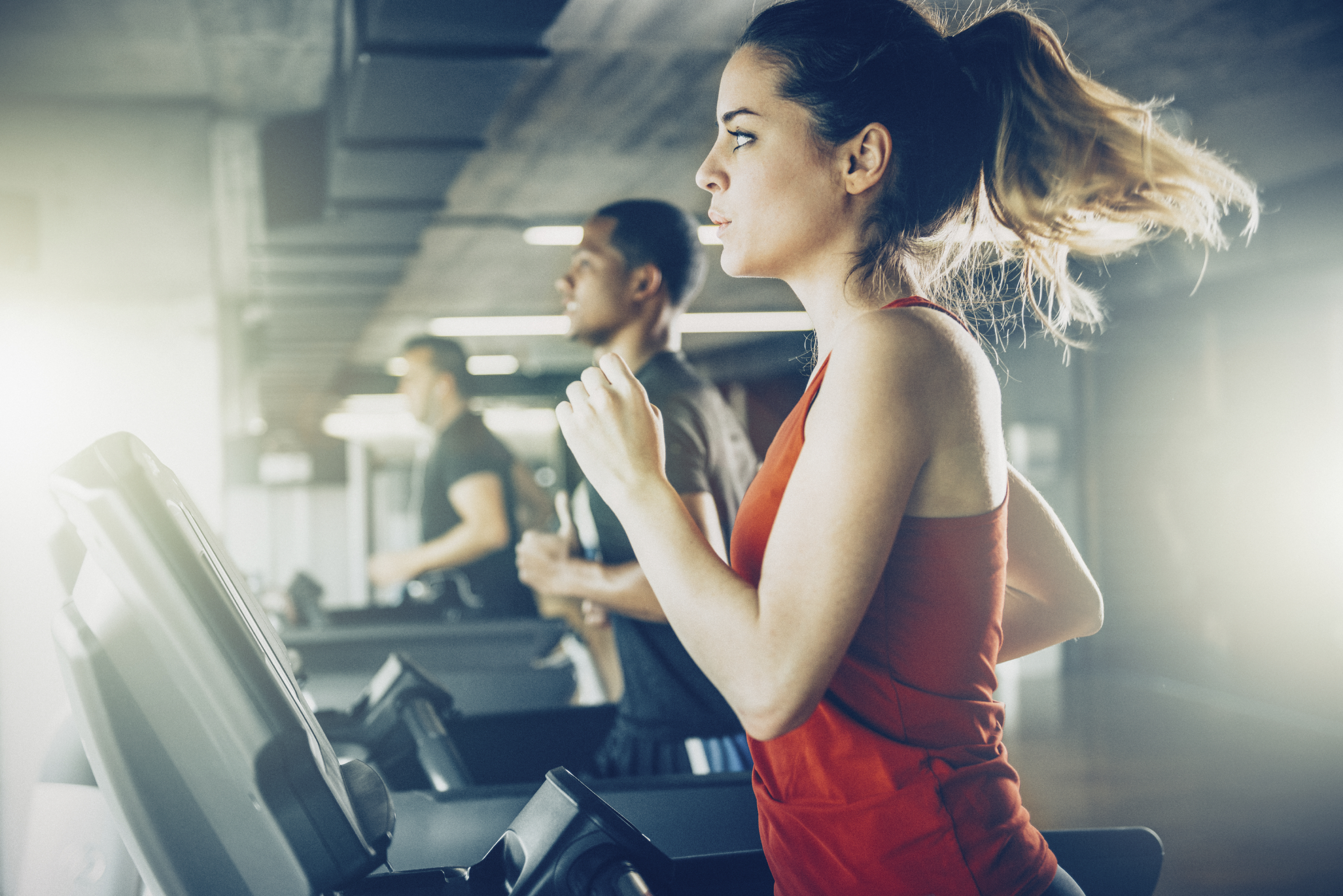 Treadmill & runners at a gym setting